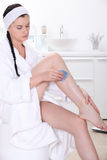 Woman epilating her legs Royalty Free Stock Photo