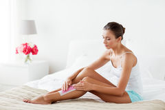 Woman epilating leg hair with wax strip at home Royalty Free Stock Photography
