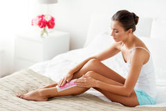 Woman epilating leg hair with wax strip at home Royalty Free Stock Photo
