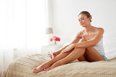 Woman with epilator removing hair on legs at home Stock Images
