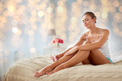 Woman with epilator removing hair on legs at home Royalty Free Stock Image