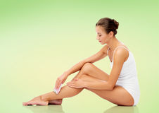 Woman with epilator removing hair on legs Stock Photography
