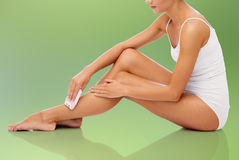 Woman with epilator removing hair on legs Royalty Free Stock Photography