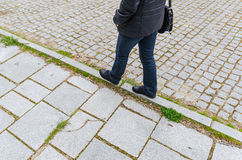 Woman equilibrium. A woman walks in equilibrium over a line in the street Stock Photo