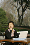Woman with er loptop. Woman studying on PC in park Royalty Free Stock Photography