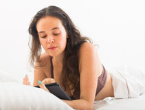 Woman with ereader lying in bed Royalty Free Stock Photos