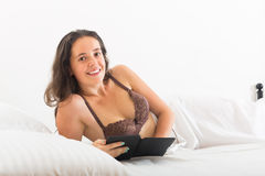 Woman with ereader lying in bed Royalty Free Stock Photography