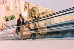 Woman on escalator Stock Photos