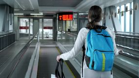 Woman on escalator with backpack and suitcase in airport terminal. Young woman traveller on escalator with backpack and suitcase in airport terminal. She is stock video