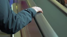 Woman on escalator close up at hand. Hand holding the escalator handrail. While moving up stock footage
