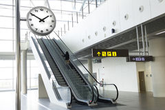 Woman on escalator next to the clock at the airport. Picture of a woman with her suitcase up the escalator at an airport Royalty Free Stock Images
