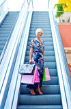 Woman on escalator stairs in shopping. Attractive woman with bags at the shopping mall escalator stairs Stock Photography