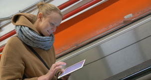 Woman on escalator using tablet computer stock video