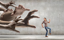 Woman escape from hand. Young woman in casual running away from big hand Royalty Free Stock Photography