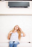 Woman escapes from the heat under the air conditioner Royalty Free Stock Images