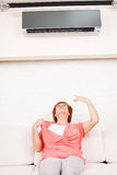 Woman escapes from the heat under the air. Conditioner at home. Happy mature woman on sofa Royalty Free Stock Image
