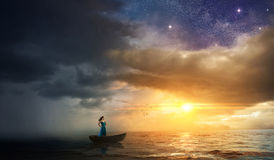 Woman escaping storm. A woman on a boat tries to escape a storm and go towards the sunset Royalty Free Stock Image