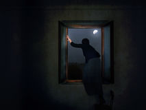 Woman escaping through window. Fugitive? Runaway? Escaping domestic violence? Or a criminal leaving the crime scene stock photo