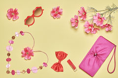 Woman essentials fashion accessories set, romantic. Stylish handbag clutch, red sunglasses, lipstick, bow, necklace and summer flowers. Woman essentials fashion Royalty Free Stock Photos