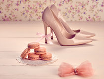 Woman essentials, fashion high heels. Macarons. Woman essentials fashion accessories. Macarons french dessert, luxury beige shoes high heels, bow. Creative Royalty Free Stock Photography