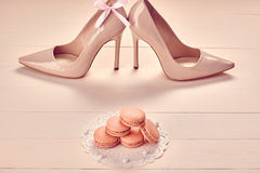Woman essentials, fashion high heels. Macarons. Woman essentials fashion accessories. Macarons french dessert, luxury beige shoes high heels, pearl, bow Royalty Free Stock Photos