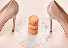 Woman essentials, fashion high heels. Macarons. Woman essentials fashion accessories. Macarons french dessert, luxury beige shoes high heels, pearl. Creative Royalty Free Stock Photo