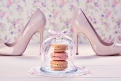 Woman essentials, fashion high heels. Macarons. Woman essentials fashion accessories. Macarons french dessert, luxury beige shoes high heels, pearl, ribbon Stock Photo
