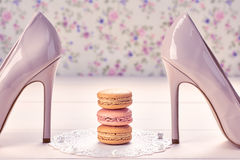 Woman essentials, fashion high heels. Macarons. Woman essentials fashion accessories. Macarons french dessert, luxury beige shoes high heels, pearl, ribbon Stock Photography
