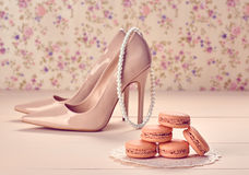 Woman essentials, fashion high heels. Macarons. Woman essentials fashion accessories. Macarons french dessert, pearl necklace, luxury beige shoes high heels Royalty Free Stock Photography