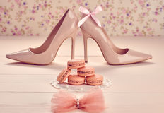 Woman essentials, fashion high heels. Macarons. Still life. Woman essentials fashion accessories. Macarons french dessert, luxury beige shoes high heels, bow Royalty Free Stock Images