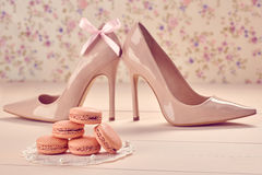 Woman essentials, fashion high heels. Macarons. Still life. Woman essentials fashion accessories. Macarons french dessert, luxury beige shoes high heels, pearl Royalty Free Stock Photography
