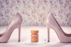 Woman essentials, fashion high heels. Macarons. Still life. Woman essentials fashion accessories. Macarons french dessert, luxury beige shoes high heels, pearl Stock Images