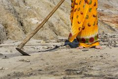Barren wasteland. A woman in an ethnic bright dress with a primitive hoe trying to cultivate dry hard barren sandy earth royalty free stock photo
