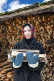 Woman in ethnic costume with firewood Stock Photography