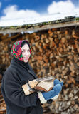 Woman in ethnic costume with firewood Royalty Free Stock Image