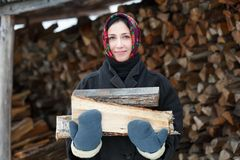 Woman in ethnic costume with firewood Royalty Free Stock Photos