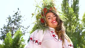 Woman in ethnic costume modelling outside. Portrait of pretty woman in ethnic costume and bright makeup smiling at camera in sunshine outside. Low angle of stock video footage