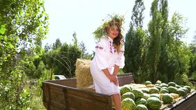 Woman in ethnic costume modelling in rural landscape. Smiling brunette in ethnic costume standing in old trailer with watermelons and haystack. Young woman stock video