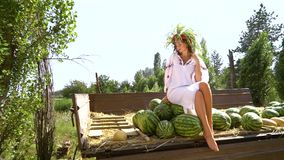 Woman in ethnic dress sitting on watermelons in countryside. Pan shot of woman in ethnic dress sitting on watermelons in trailer. Attractive brunette posing and stock footage