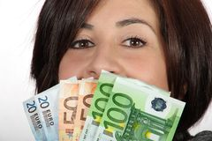 Woman with euro bills. Woman with purple jacket and gray scarf with with euro bills stock photos