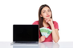 Woman with euro cash showing blank laptop screen Royalty Free Stock Image