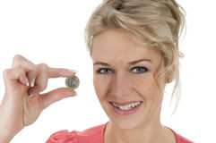 Woman with euro coin between her fingers. Happy smiling young woman holding one Euro coin Royalty Free Stock Photo