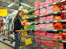 Woman of european appearance makes purchases in the store, in the department of linen and groceries. Woman making purchase at stor Stock Photography