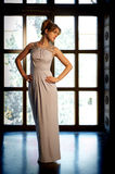 Woman in Evening Dress. Beautiful Young Woman in Evening Dress Standing at the Window Royalty Free Stock Images