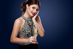 Woman in evening dress with champagne glasses - new year, celebration. On dark blue background Royalty Free Stock Photo