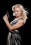 Woman in evening dress holding gun. Portrait of blonde woman in evening dress holding gun isolated on black Stock Photography