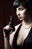 Woman in evening dress holds gun Stock Photo