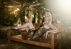 Woman in an evening dress lies on a bench under a palm tree at night Royalty Free Stock Photo