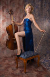 Woman in evening dress posing with cello Stock Images