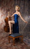 Woman in evening dress posing with cello Stock Photography